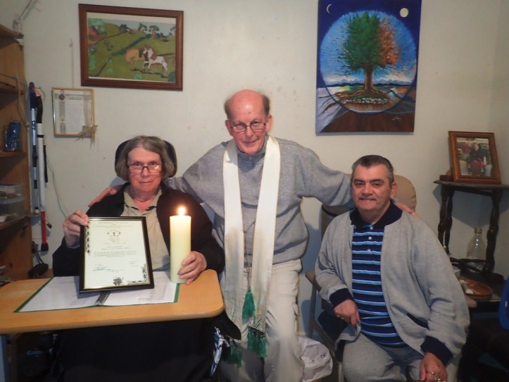 Jessica holding Candle and Certificate with Shepherd Guardian Bishop Peter johnson and partner Graham.